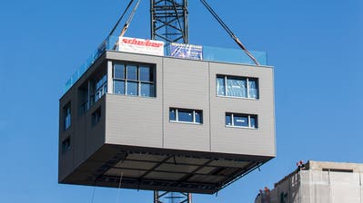 Das 115 Tonnen schwere zweistöckige Haus wird mit diesem Kran auf das 28 Meter hohe Silo rechts gehievt. (Bild: Alexandra Wey/Keystone)
