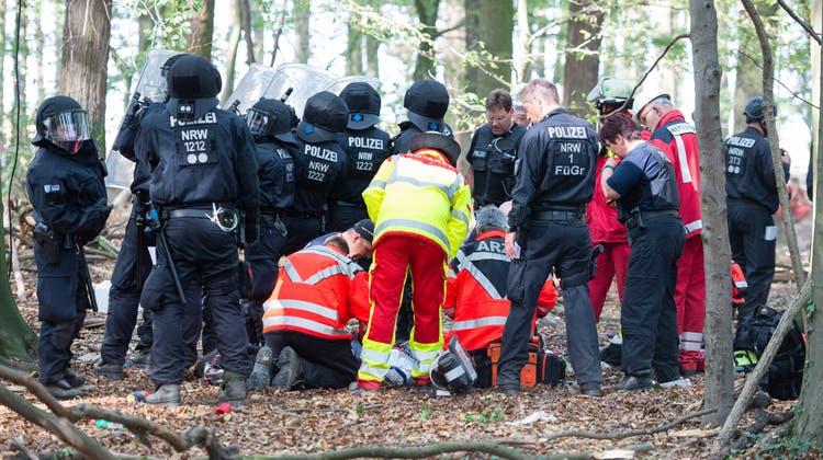 Notärzte versorgen den Mann, der von einem Baumhaus im Hambacher Forst gefallen ist. (Bild: Keystone/Christophe Gateau (Kerpen, 19. September 2018))