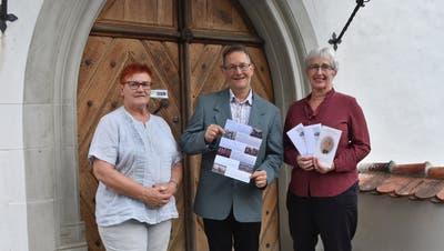 Barbara Binzegger, Christoph Honegger und Renée Franck vom Verein Freunde vor der Klosterkirche Paradies mit dem Konzertprogramm 2018/19. (Bild: Thomas Güntert)