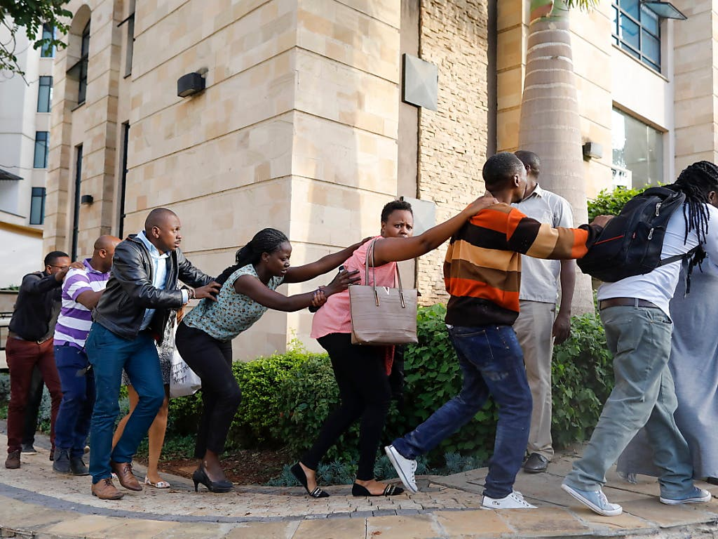 Zahlreiche Menschen werden aus einem Luxushotel in Nairobi geleitet, nachdem auf das Gebäude ein Anschlag verübt worden war. (Bild: KEYSTONE/EPA/DAI KUROKAWA)