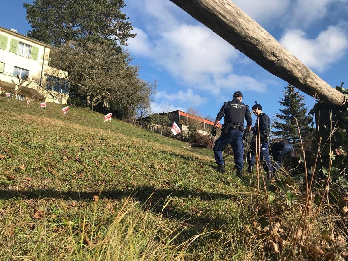 Die Polizisten suchen das Nachbargrundstück ab. Die 66-Jährige wurde vor dem Haus im Hintergrund (Erlinsbacherstrasse 40) gefunden. (Bild: Stefania Telesca (Aarau, 18. Januar 2019))