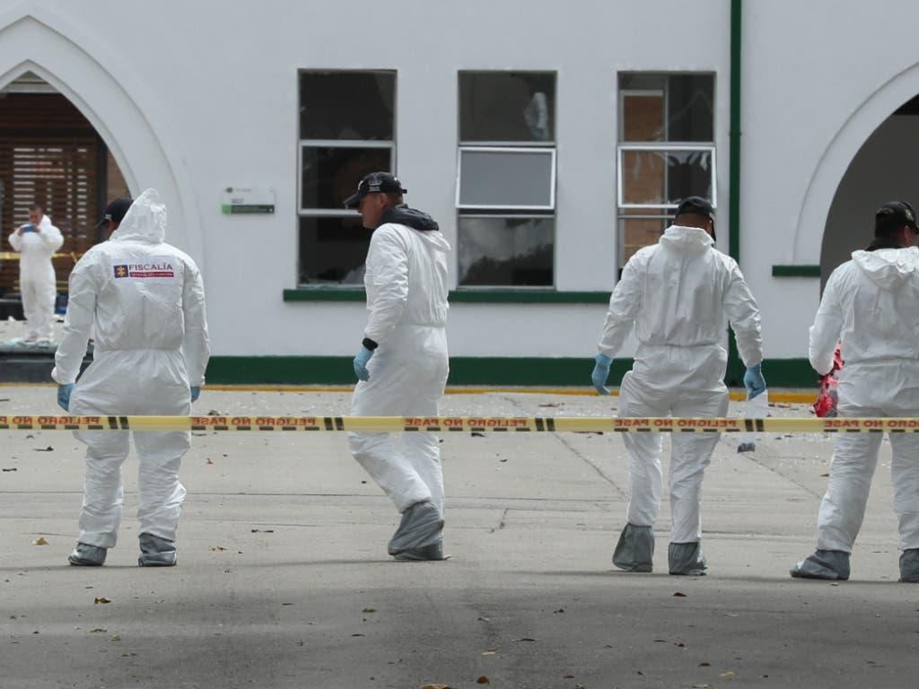 Forensiker suchen nach kleinsten Hinweisen auf die Urheberschaft des Anschlags auf eine Polizeischule in Kolumbien. (Bild: KEYSTONE/EPA EFE/MAURICIO DUENAS CASTANEDA)