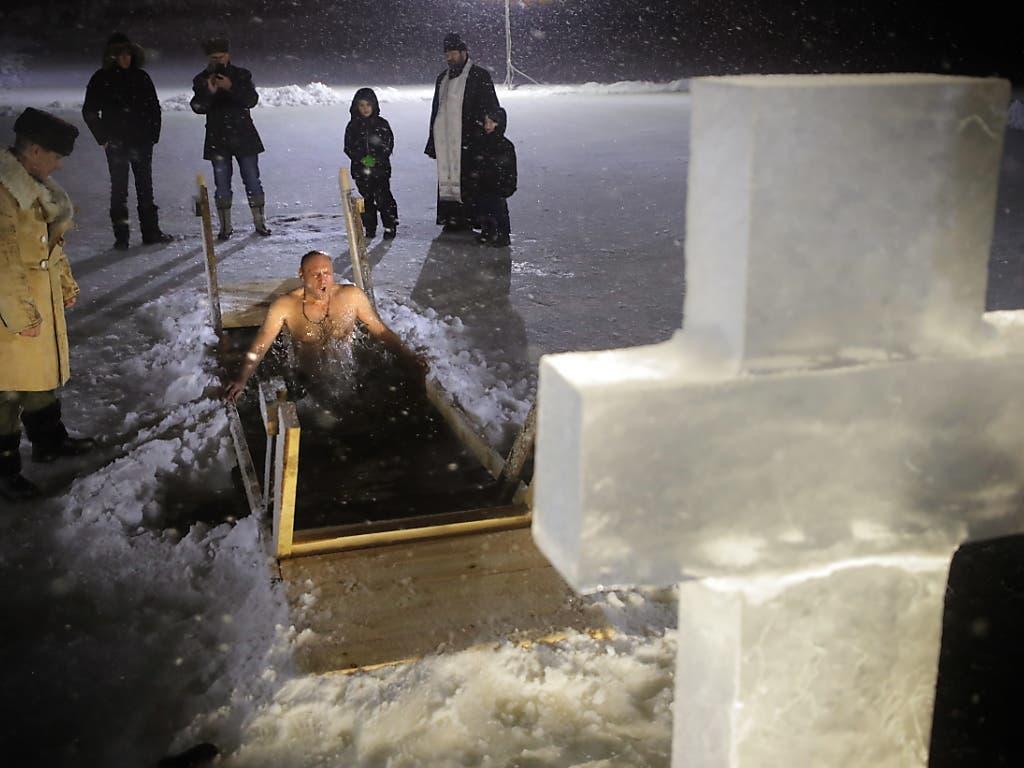 Ins Eiswasser für den Glauben: Gläubiger ausserhalb von Moskau unter dem Eiskreuz beim frostigen Vergnügen. (Bild: KEYSTONE/EPA/MAXIM SHIPENKOV)