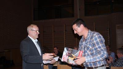 Kommandant Christian Feuz übergibt Roland Kauderer eine Broschüre, die dessen Wirken würdigt. (Bild: Trudi Krieg)