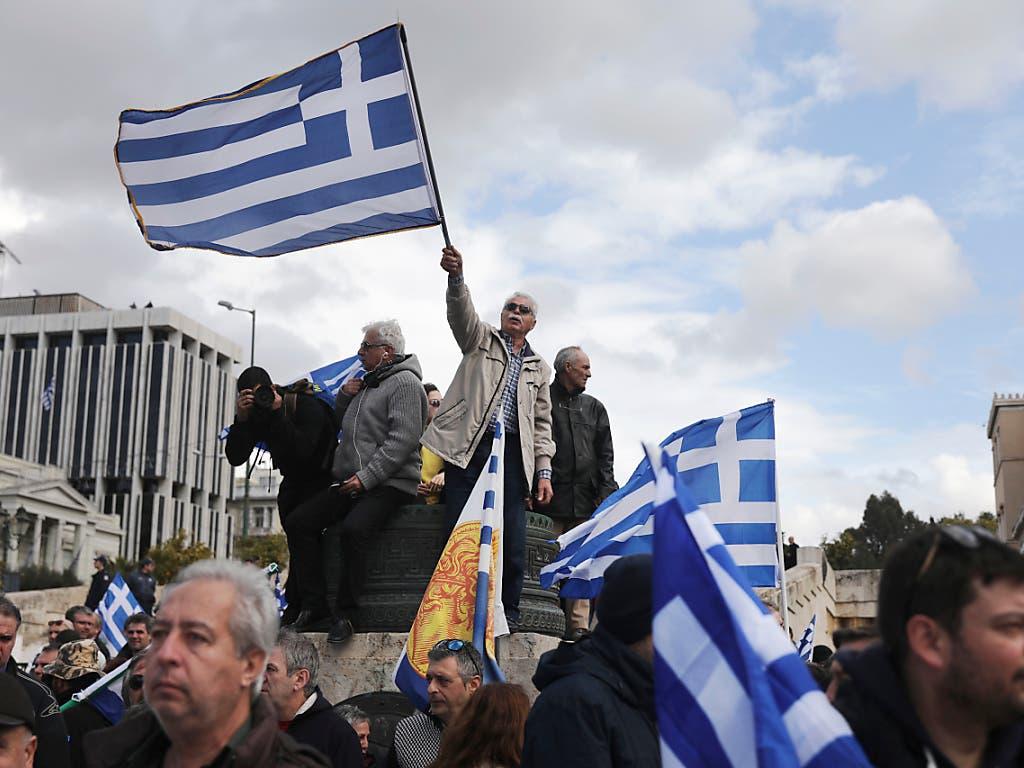 Demonstranten schwenken griechische Flaggen vor dem Parlament in Athen. Sie sind dagegen, dass ihr nördliches Nachbarland künftig Nordmazedonien heisst. (Bild: Keystone/AP/Yorgos Karahalis)