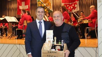 Gemeindepräsident Urs Forster ehrt Walter Gilg für dessen Engagement für die Feuerwehr mit einem «Manne-Täschli». (Bild: Manuela Olgiati)