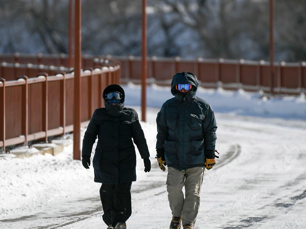 Gut «verpackte» Spaziergänger in Minneapolis: Einige Bundesstaaten haben wegen der Kälte den Katastrophenfall ausgerufen. (Bild: KEYSTONE/EPA/CRAIG LASSIG)