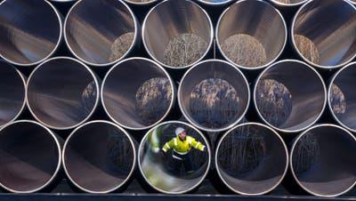 Ein Arbeiter inspiziert einen tonnenschweren Rohrstapel, der für die Gaspipeline Nord Stream 2 im Sassnitzer Hafen im Nordosten Deutschlands verwendet wird. (Bild: Jens Buettner/EPA (Rügen, 6. Dezember 2016))