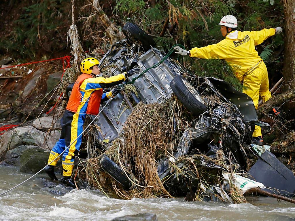 Rettungskräfte bergen nach dem Taifun «Hagibis» ein Autowrack aus einem Fluss bei Koriyama in der Nähe von Fukushima. (Bild: KEYSTONE/AP Kyodo News/KOTA ENDO)