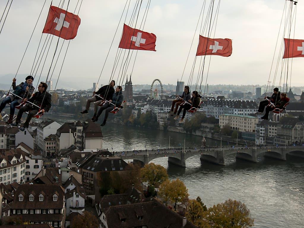 Besucher vergnügen sich auf der «Condor» beim Kasernenareal an der Herbstmesse in Basel, im Hintergrund das Riesenrad beim Münster. (Bild: KEYSTONE/ALEXANDRA WEY)