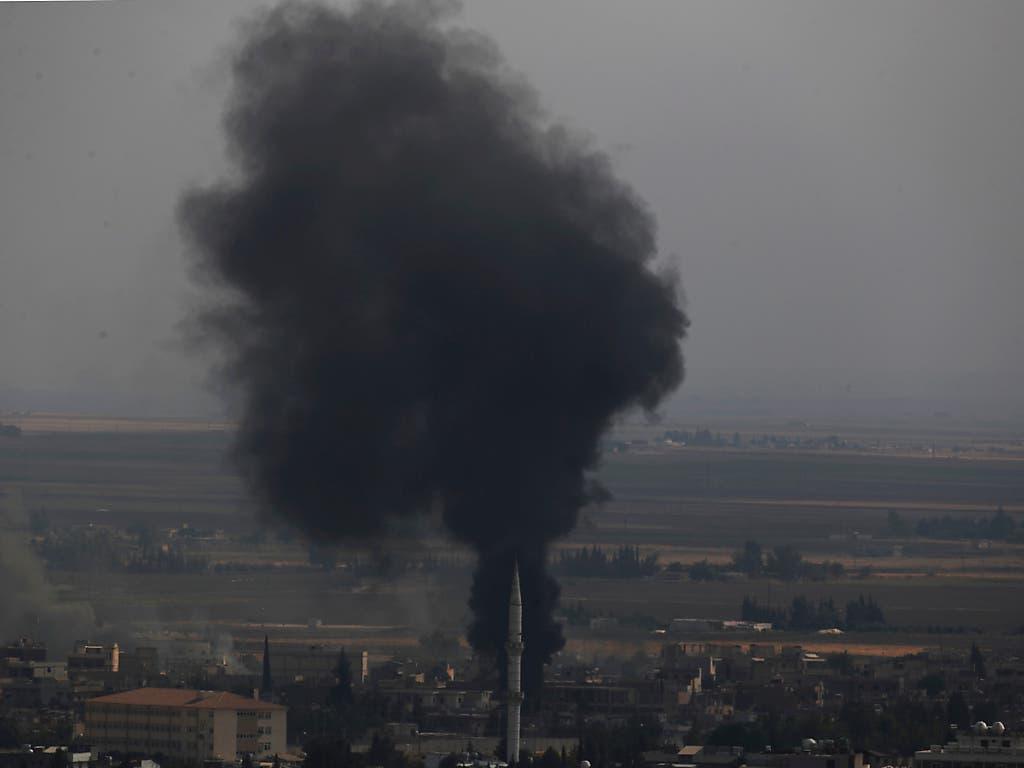 Die kurdische YPG-Miliz leistete am Mittwoch in der nordsyrischen Grenzstadt Ras al-Ain weiter erbitterten Widerstand. Die Kämpfer zündeten Reifen an, um mit dem Rauch den türkischen Kampfjets die Sicht zu erschweren. (Bild: KEYSTONE/AP/LEFTERIS PITARAKIS)