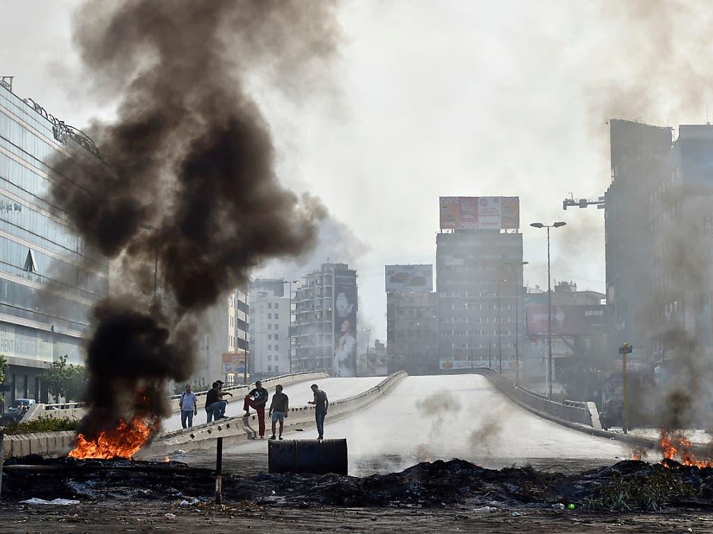 Aus Protest gegen die Regierung haben Demonstranten in Beirut Strassenbarrikaden errichtet und Pneus angezündet. (Bild: KEYSTONE/EPA/WAEL HAMZEH)