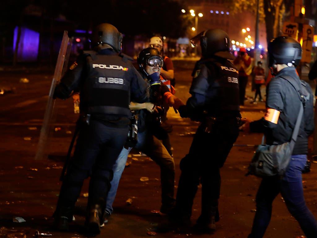 Polizisten nehmen bei den Protesten in Barcelona am Abend einen Fotografen der Zeitung «El Pais» fest. (Bild: KEYSTONE/AP/MANU FERNANDEZ)