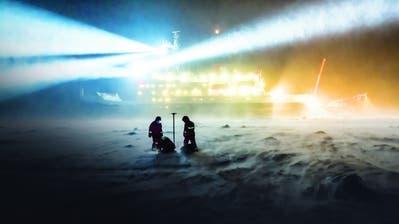 Forscher vergraben ein Stromkabel im Eis. (Bild: Stefan Hendricks/ Alfred-Wegener-Institut, Antarktis, 16. Oktober 2019)