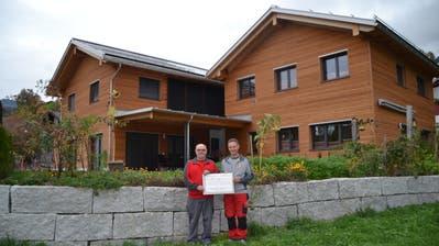 Bauherr und Architekt Ernst Giger (links) und Hansjörg Roth mit dem Diplom «PlusEnergieBau». (Bild: Adi Lippuner)