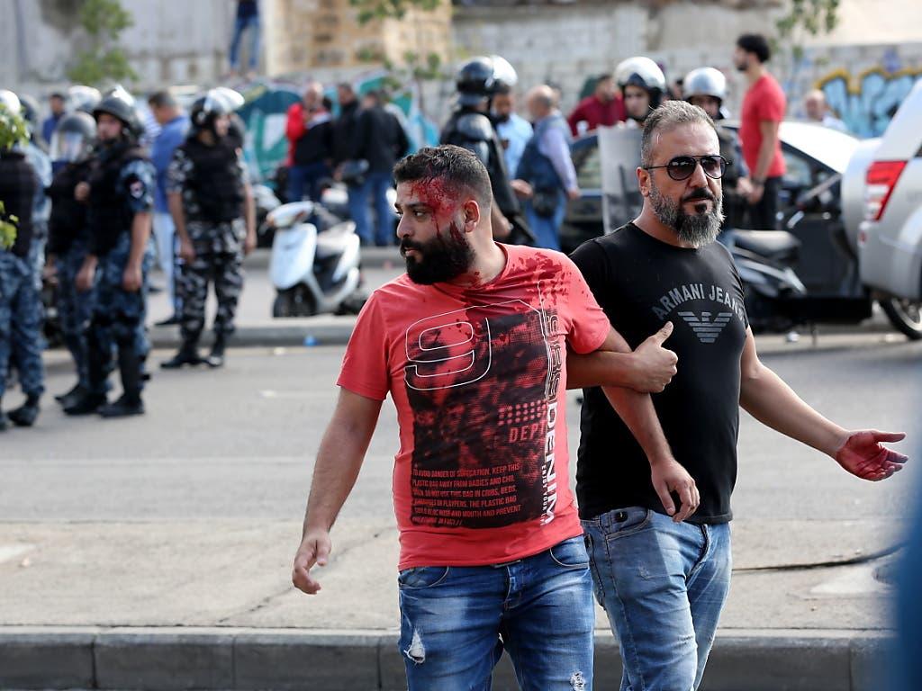 Die Hisbollah greift Protestler an: Ein Verletzter wird in Beirut nach einer Auseinandersetzung weggeführt. (Bild: KEYSTONE/EPA/NABIL MOUNZER)