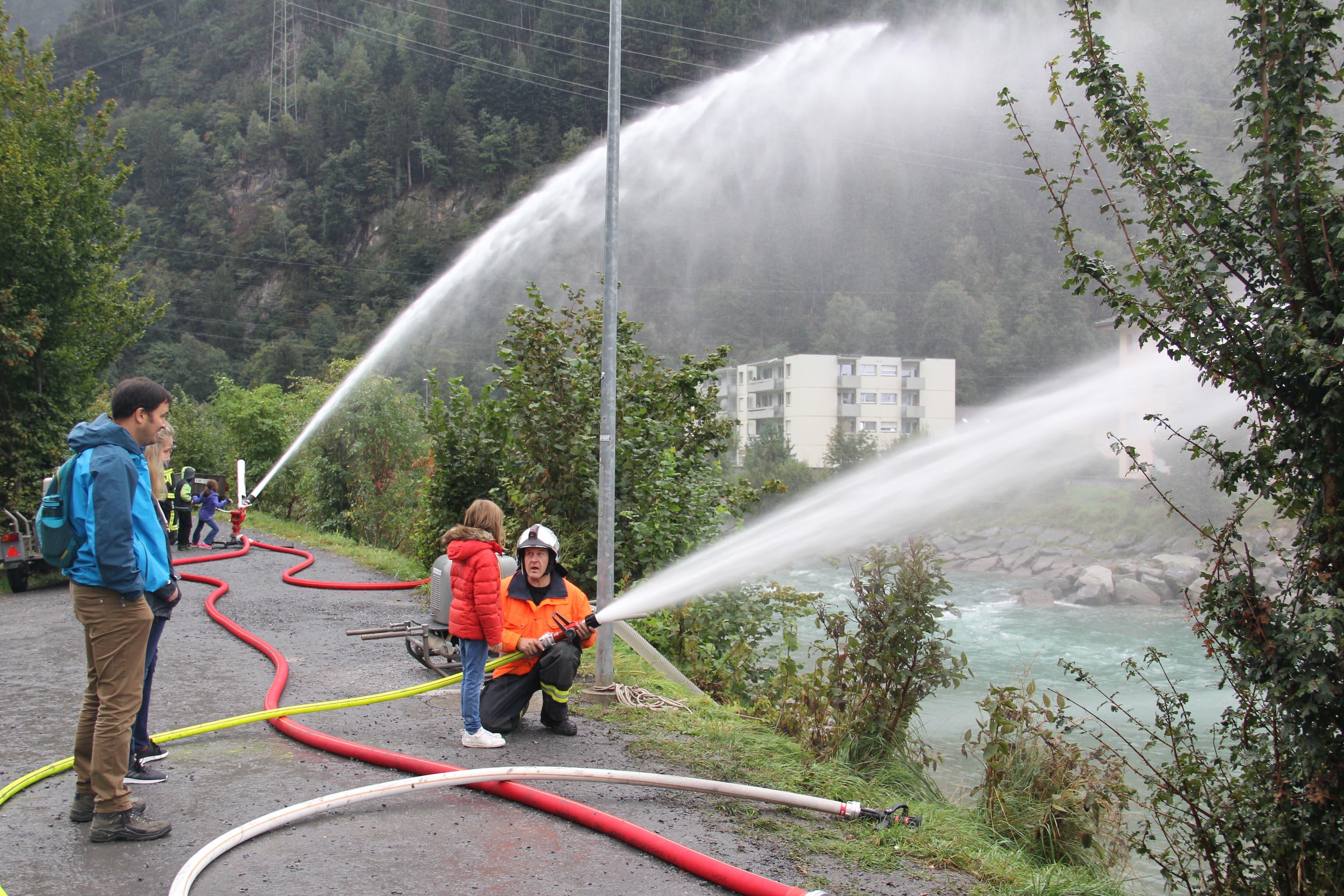 Feuerwehrmann Michael Stadler erklärt einem Mädchen, wie das Strahlrohr zu bedienen ist. (Bild: Paul Gwerder, Erstfeld, 5. Oktober 2019)