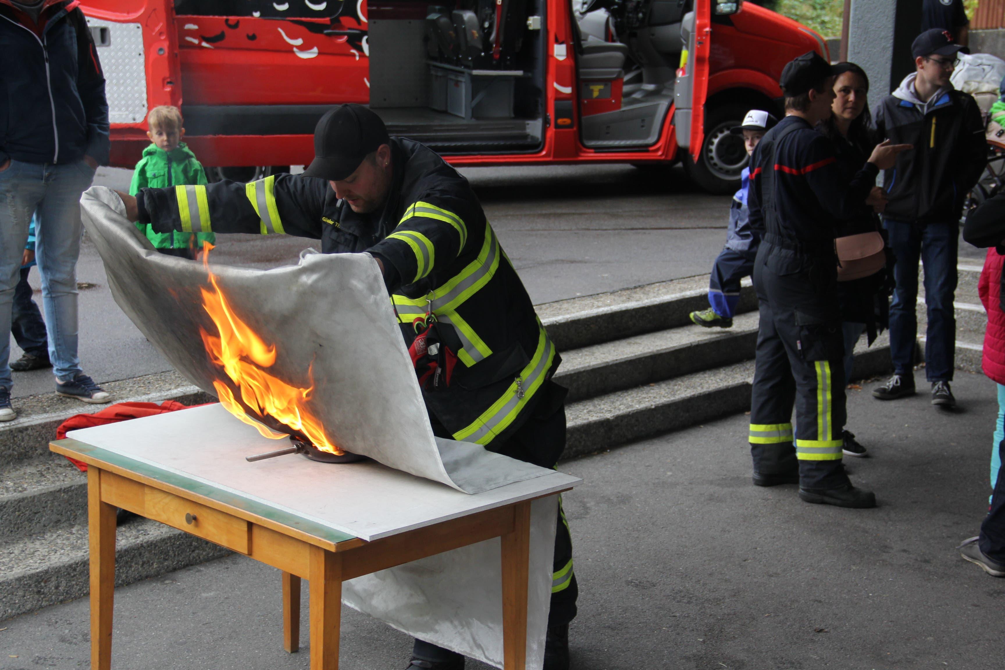 Christian Gisler demonstriert, wie ein Brand einer Bratpfanne mit der Löschdecke bekämpft wird. (Bild: Paul Gwerder, Erstfeld, 5. Oktober 2019)
