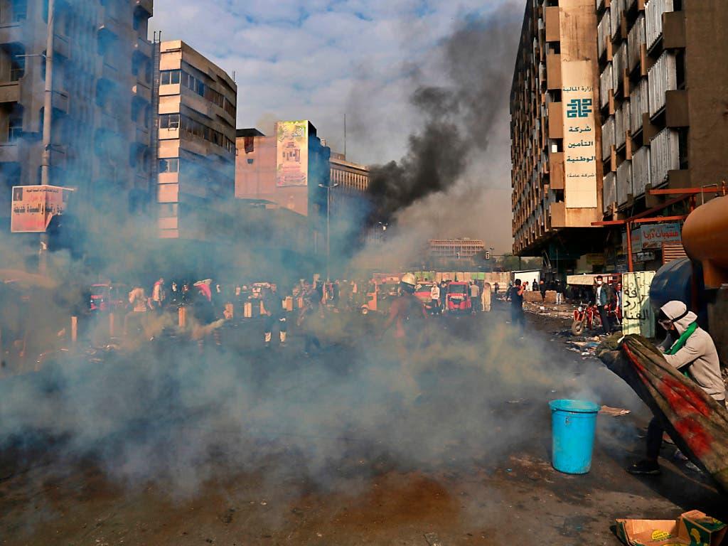 Ein Demonstrant in Bagdad versucht sich mit einer Decke vor Tränengas-Granaten zu schützen. Seit Beginn der Proteste Anfang Oktober wurden laut Uno bereits etwa 20 Menschen durch Tränengas-Granaten getötet. Den meisten Opfern zertrümmerten die Geschosse den Schädel. (Bild: KEYSTONE/AP/KHALID MOHAMMED)