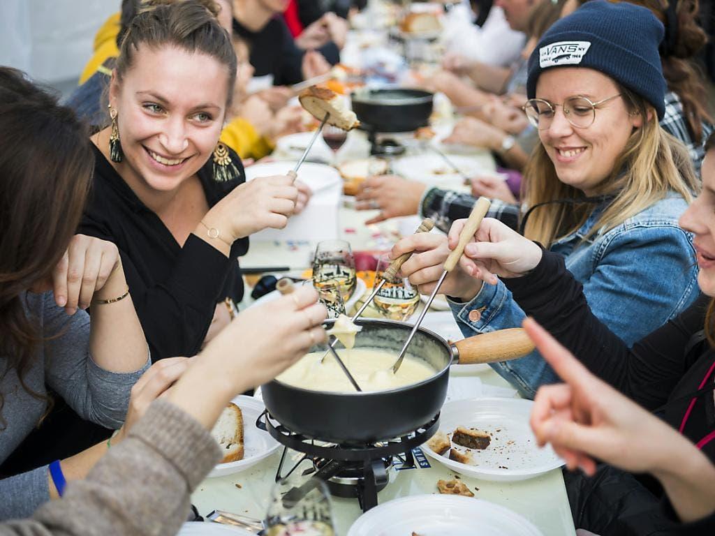 Keine Spur von Konkurrenzkampf an dieser Weltmeisterschaft in Tartegnin (VD): Fondue kochen und essen führt bei den Besuchern zu guter Laune und ausgelassener Stimmung. (Bild: Keystone)