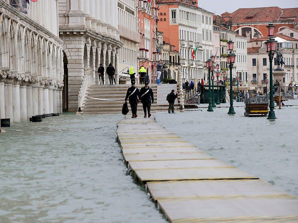Zwei Carabinieri auf einem Steg im überfluteten Venedig. (Bild: KEYSTONE/AP/LUCA BRUNO)