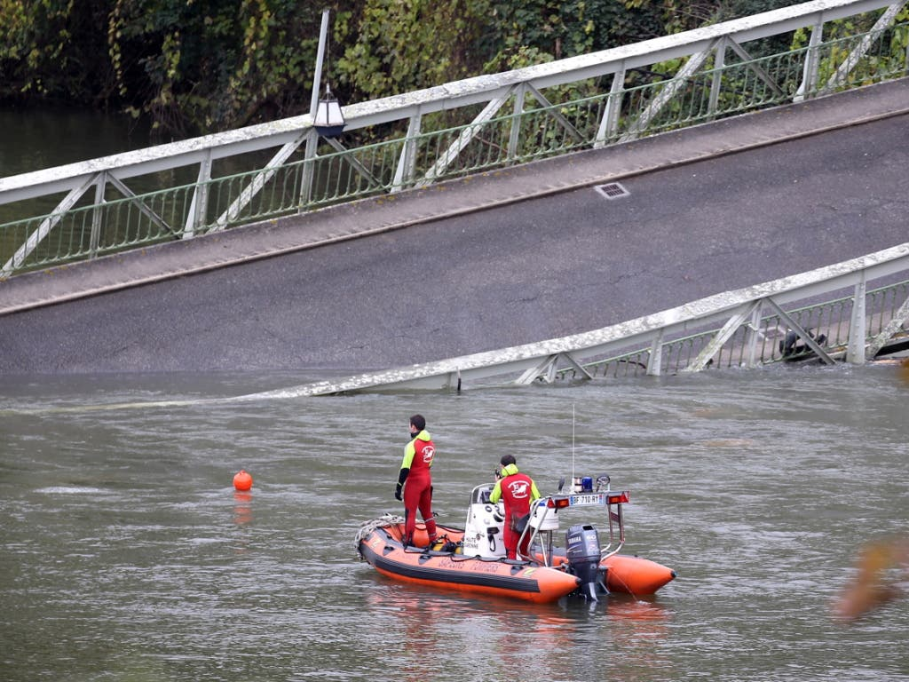 Rettungskräfte suchen im Bereich der eingestürzten Brücke nach Vermissten. (Bild: KEYSTONE/EPA/FREDERIC SCHEIBER)