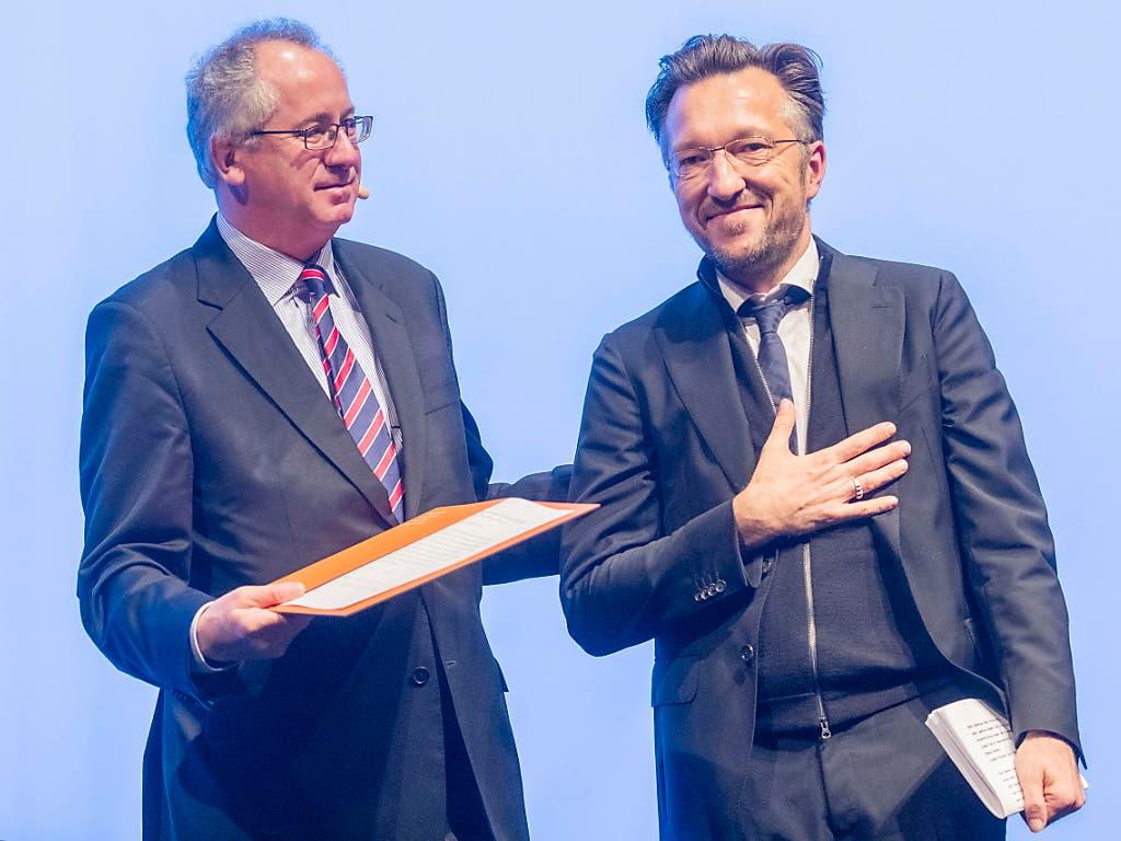 Sichtlich gerührt: Lukas Bärfuss (rechts) bei der Übergabe des Georg-Büchner-Preises durch Ernst Osterkamp, Präsident der Deutschen Akademie für Sprache und Dichtung. (Bild: KEYSTONE/EPA/ALEXANDER HEIMANN)