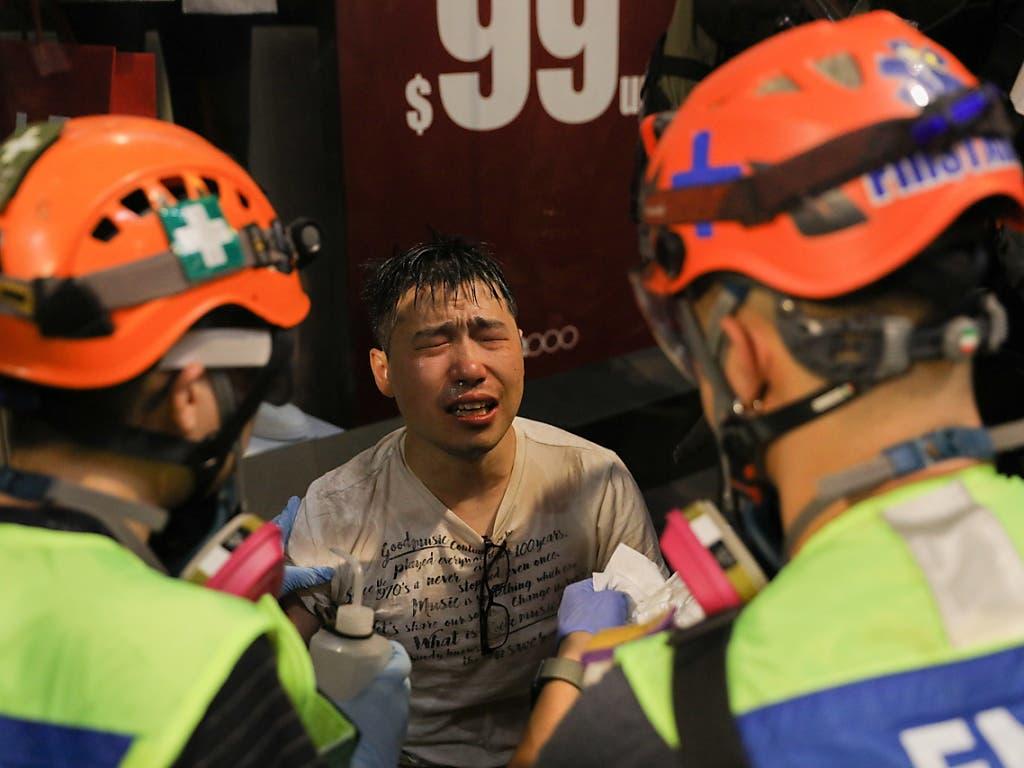 Ein Demonstrant erhält Hilfe, nachdem Pfefferspray in seine Augen geraten ist. (Bild: KEYSTONE/EPA/JEROME FAVRE)