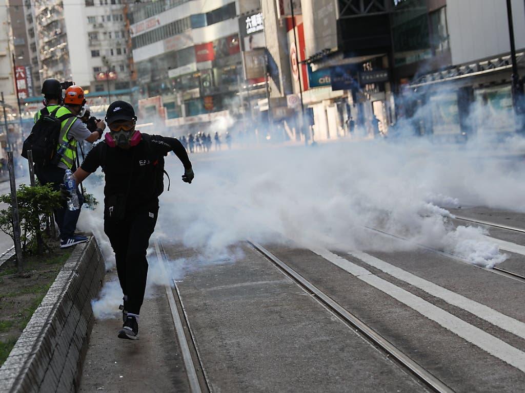 Nach dem Tränengas-Einsatz in Hongkong zerstreuten sich die Demonstranten, viele zogen in Richtung Stadtzentrum weiter, einige warfen mit Steinen. (Bild: KEYSTONE/EPA/JEROME FAVRE)
