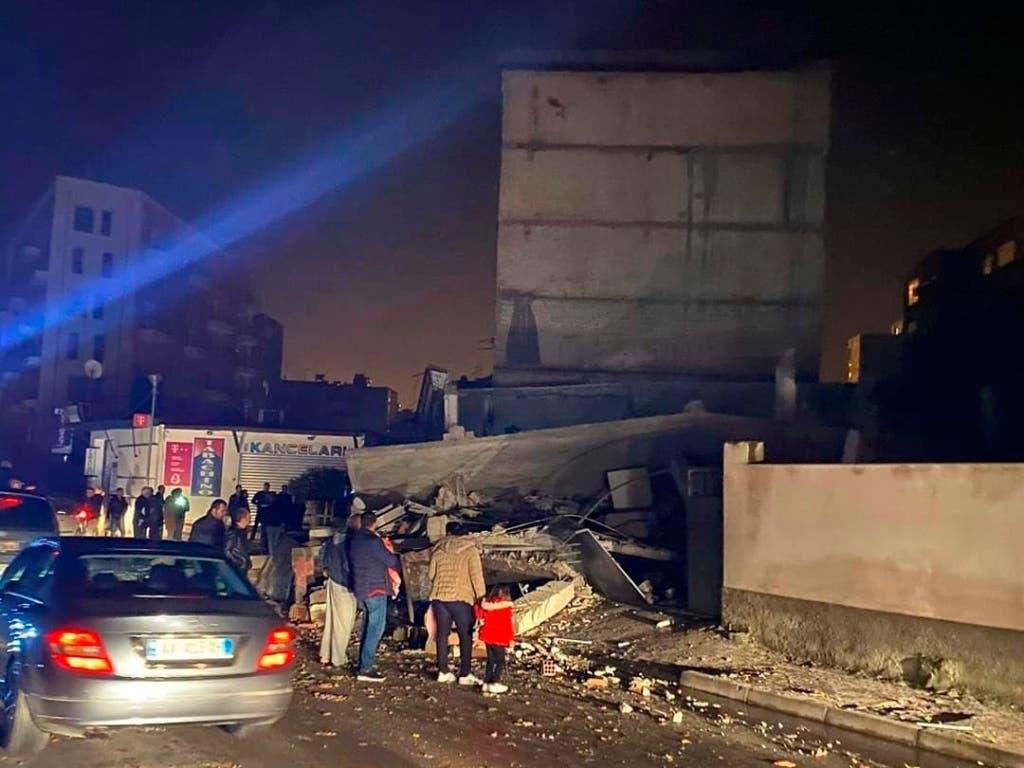 Menschen betrachten Trümmer eines eingestürzten Haues in Durres im Westen Albaniens. (Bild: KEYSTONE/AP/UNCREDITED)
