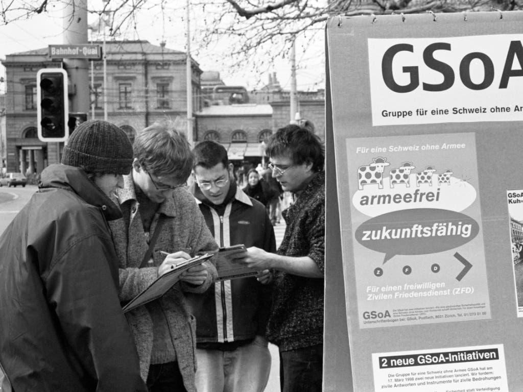 Aktivisten der «Gruppe für eine Schweiz ohne Armee» (GSoA) sammeln am 21. März 1998 auf der Bahnhofbrücke in Zürich Unterschriften für eine neue Armeeabschaffungsinitiative und eine Initiative für einen freiwilligen zivilen Friedensdienst. (Bild: KEYSTONE/STR)