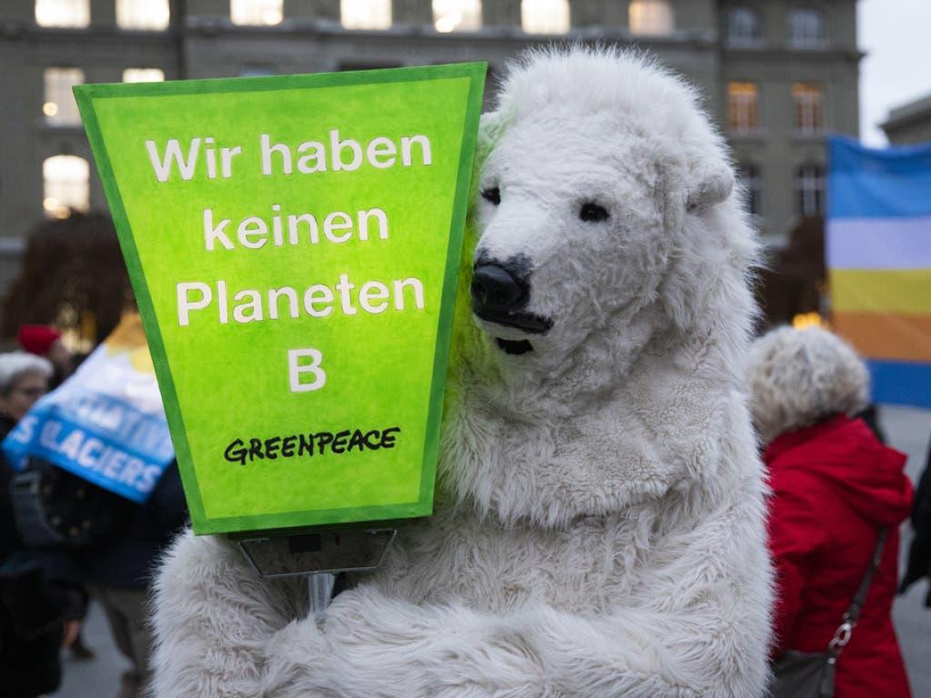 Ein Aktivist in einem Eisbärkostuem hält eine Lampe mit der Aufschrift «Wir haben keinen Planeten B», bei der Einreichung der Gletscherinitiative am Mittwoch auf dem Bundesplatz in Bern. (Bild: Keystone/PETER KLAUNZER)