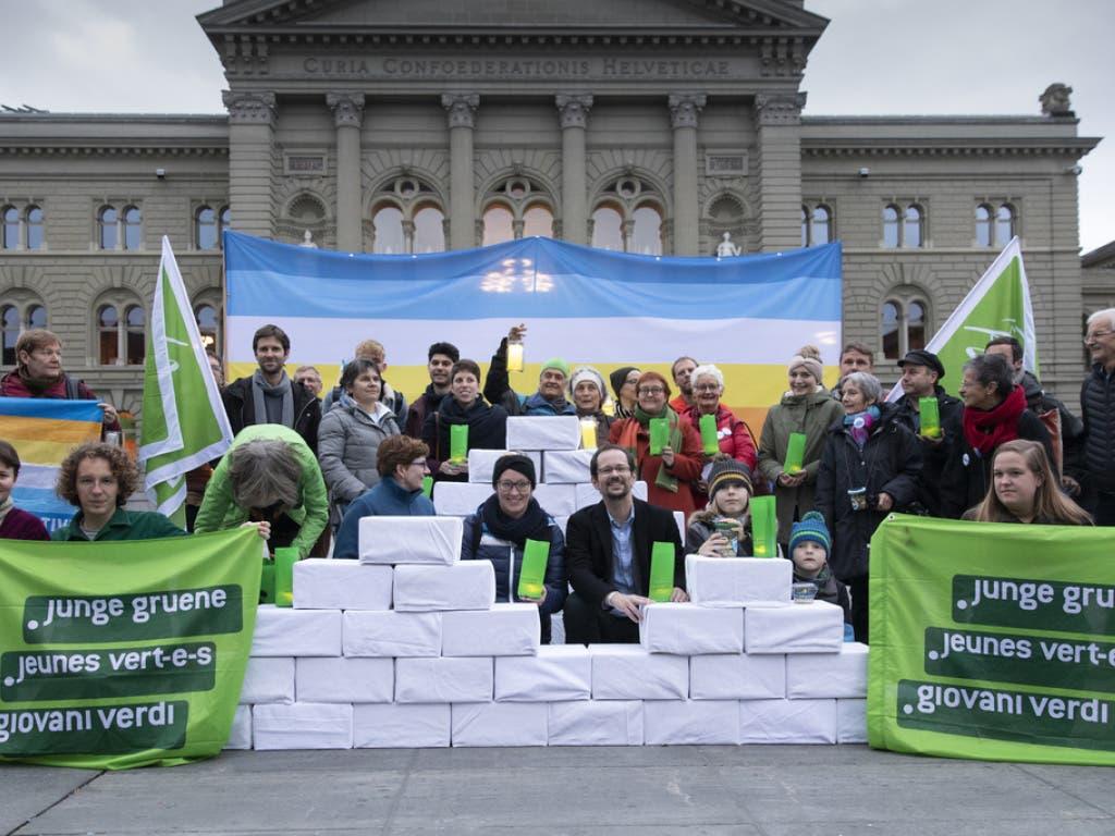 Balthasar Glättli (GPS/ZH) und Aline Trede (GPS/BE) posieren mit Mitgliedern der Grünen und jungen Grünen bei der Einreichung der Gletscherinitiative am Mittwoch auf dem Bundesplatz in Bern. (Bild: Keystone/PETER KLAUNZER)