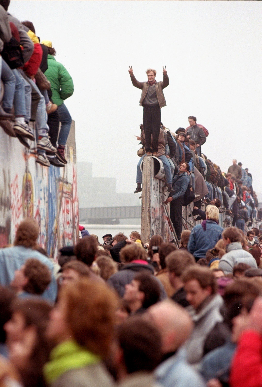 Ein Berliner feiert das Ende der Berliner Mauer. (Bild: Lionel Cironneau / Keystone / AP, 12. November 1989)