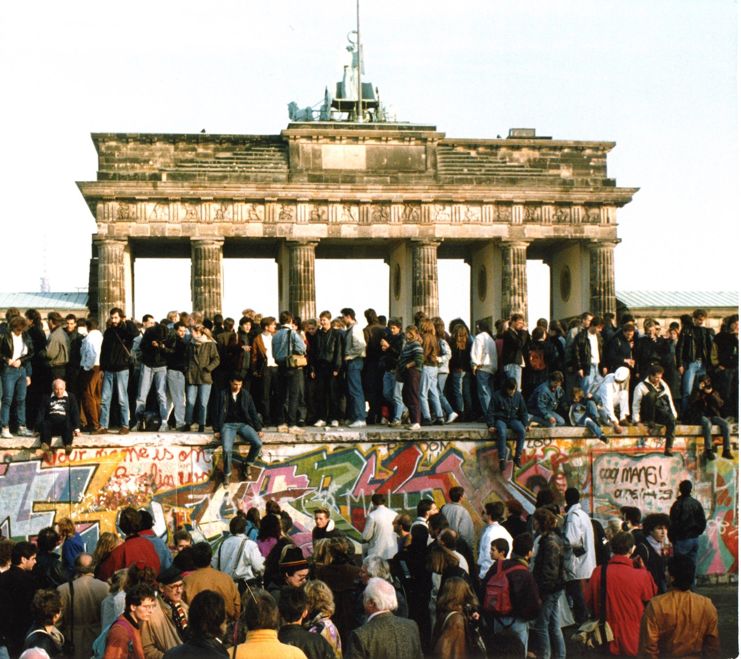 Am Tag nach der Öffnungen steigen Menschen auf die Berliner Mauer vor dem Brandenburger Tor in Berlin. (Bild: Keystone /AP, 10. November 1989)