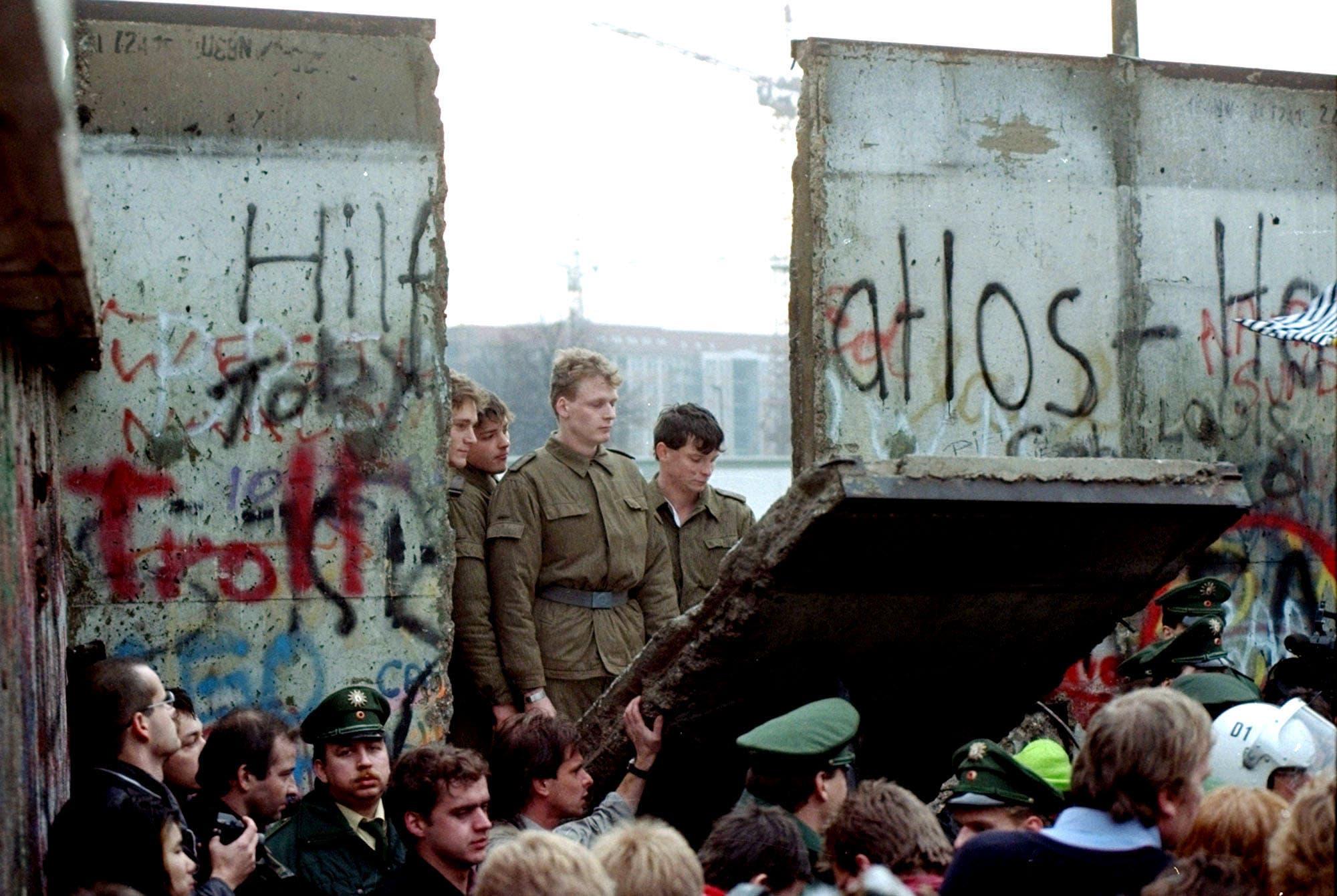 Nach 28 Jahren der Trennung begannen die Berliner nach der Grenzöffnung am 9. November 1989, die Mauer zu demontieren. Ehemalige DDR-Grenzsoldaten schauen ihnen belustigt zu. (Bild: Lionel Cironneau / Keystone, 11. November 1989)
