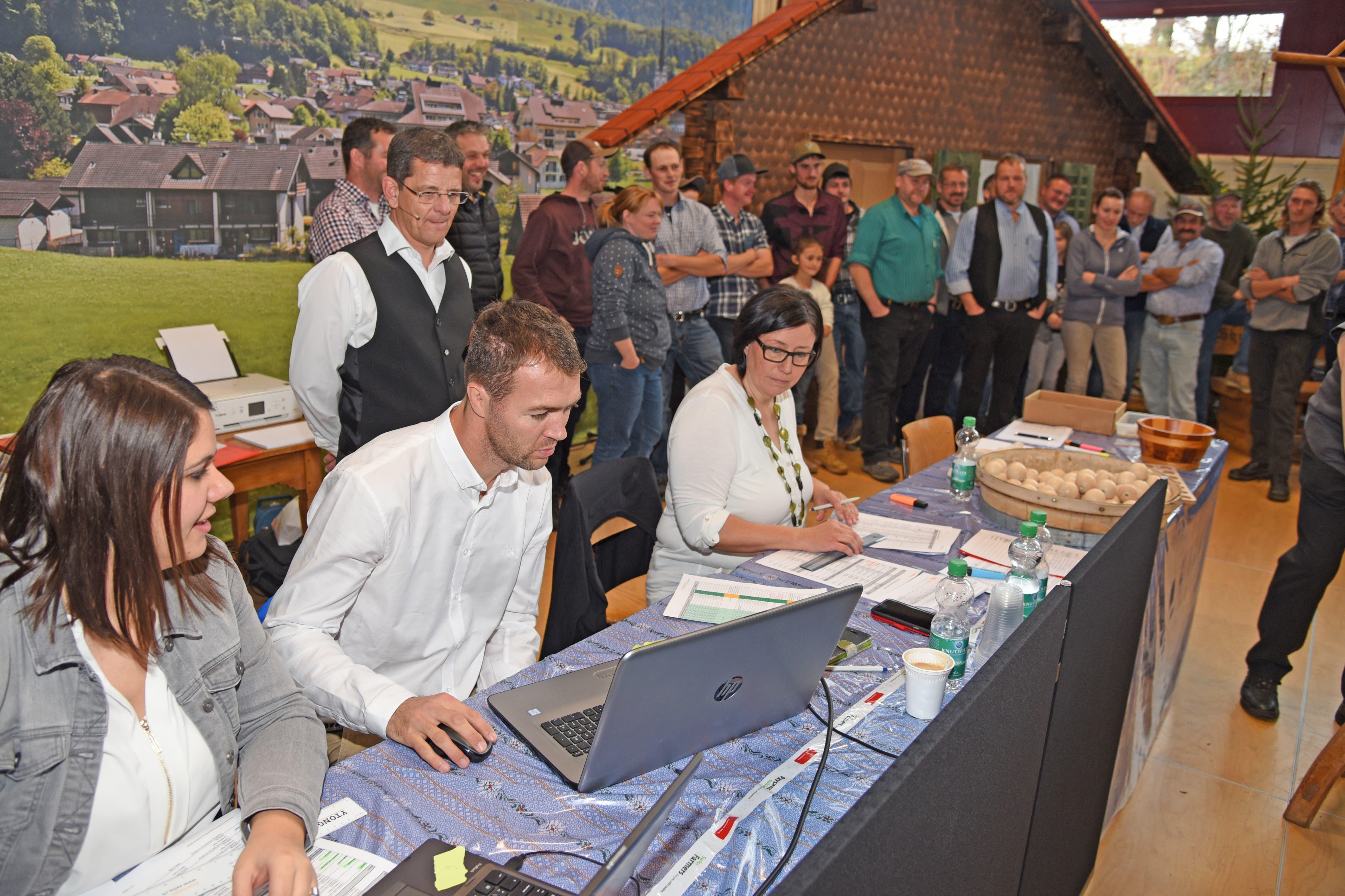Alle Vorgänge werden fein säuberlich protokolliert. Verantwortlich dafür sind Alpgenossenschreiber Thomas Bucher und seine Mitarbeiterinnen. Beobachtet von Korporationspräsident Markus Ettlin (hinten links). Rechts stehen die Bewerber für die nächste Alp.