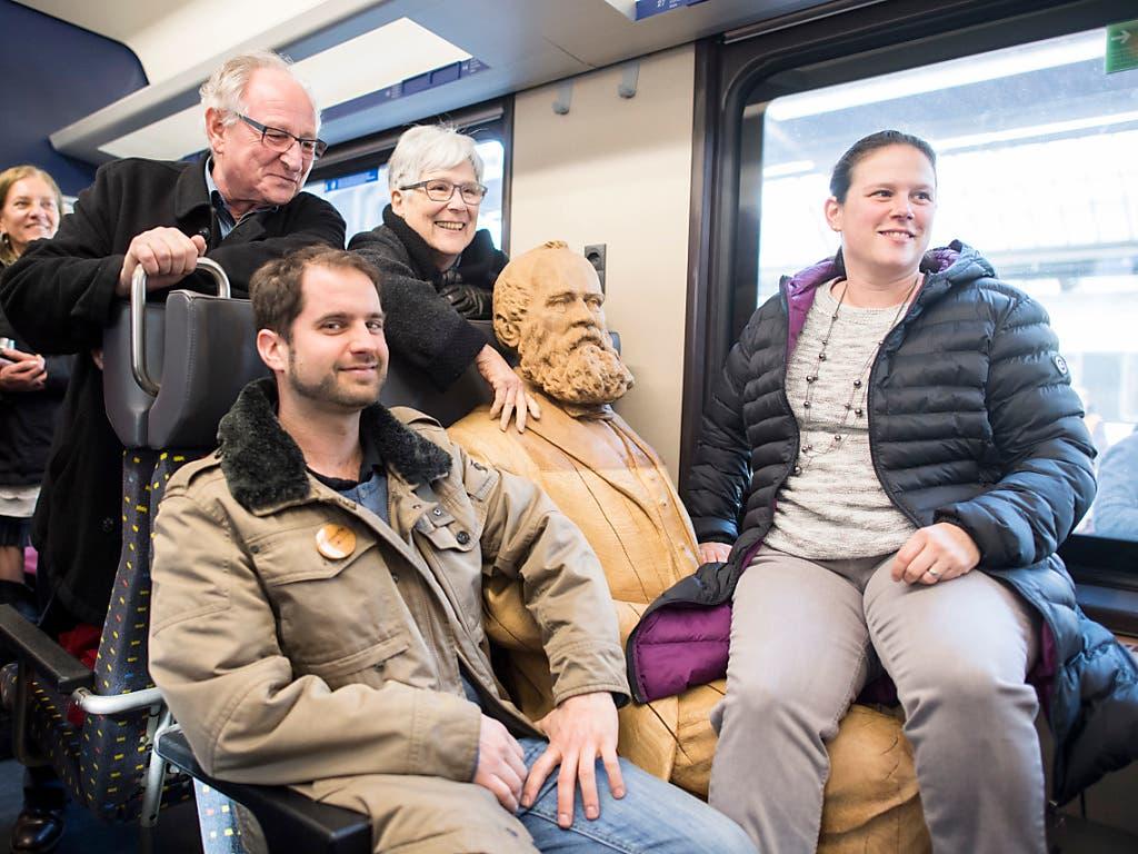 Die Schweiz ist eine Nation von Bahnfahrenden. Passagiere posieren mit einer Statue des Eisenbahnpioniers Alfred Escher.