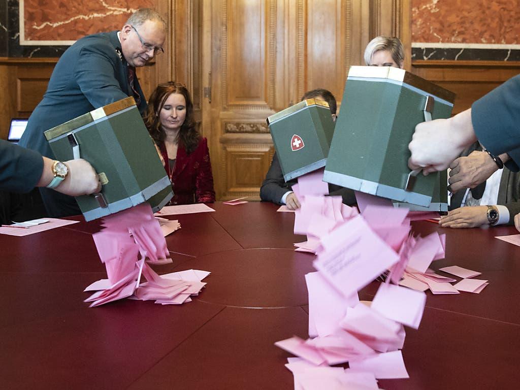 Weibel leeren bei den Stimmenzählern die Urnen mit den Wahlzetteln für die Bundesratswahlen aus.(KEYSTONE/Peter Klaunzer)