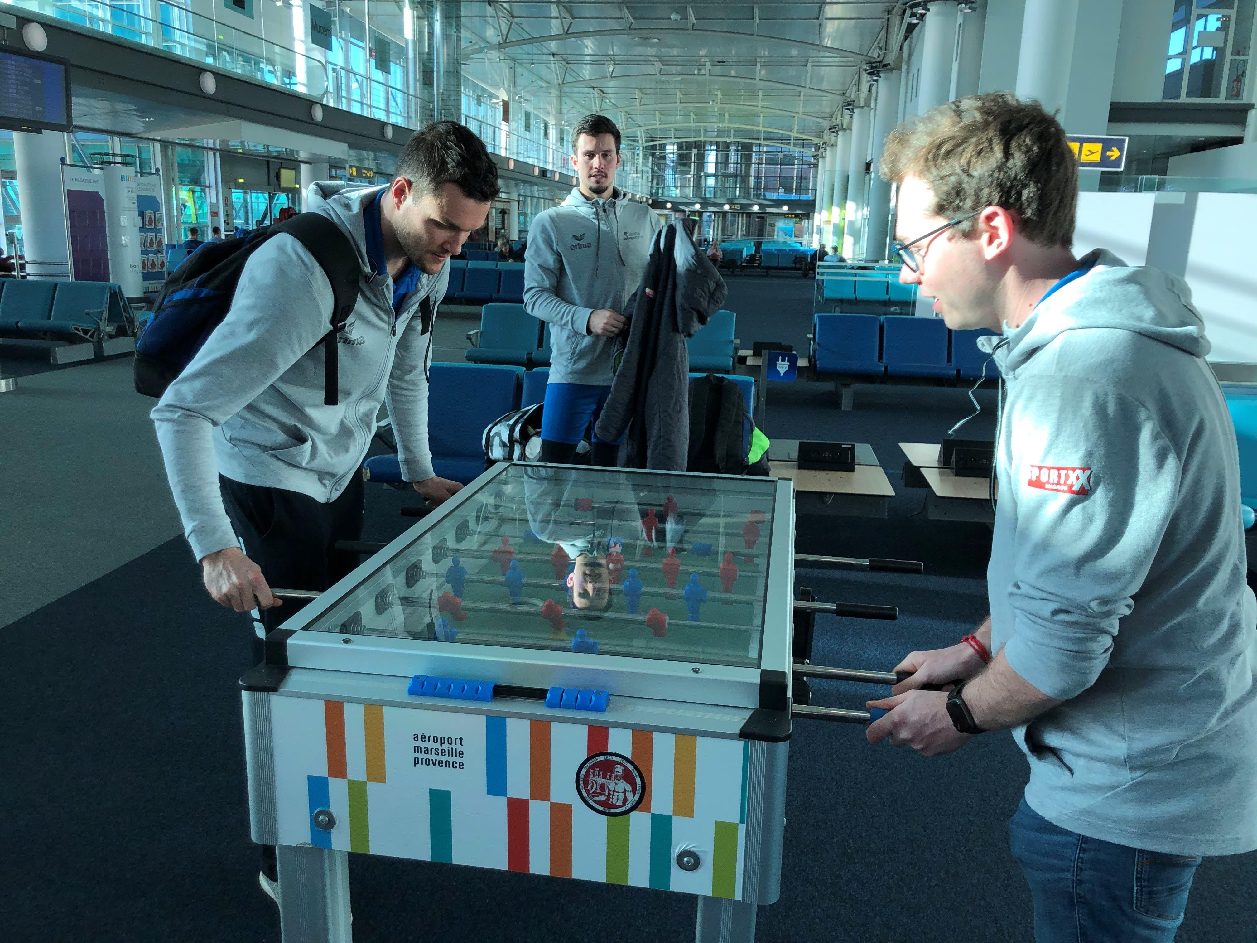 Auf dem Flug mit zwei Zwischenstopps gibt es viel Zeit totzuschlagen. Auf dem Flughafen von Marseille duellieren sich Thomas Zass (links) und Videoscout Riccardo Balsamo im Tischfussball. Jovan Djokic beobachtet das Spiel aus der Ferne.