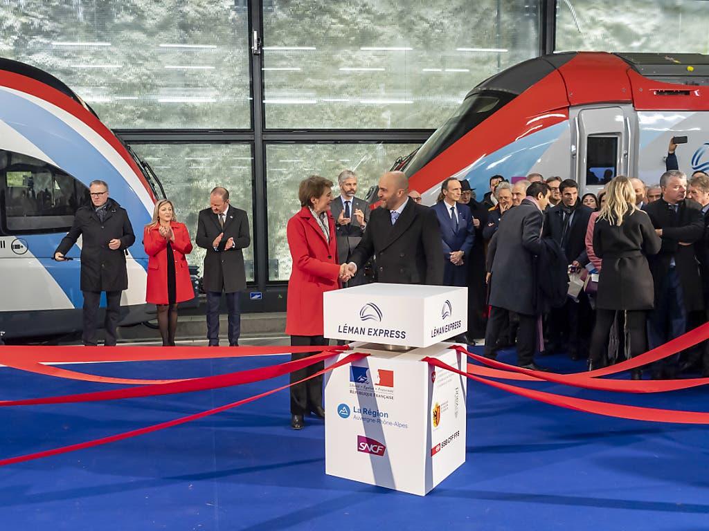 Bundesrätin Simonetta Sommaruga und der französische Botschafter in der Schweiz, Frédéric Journès, reichen sich bei der Einweihungsfeier für den neuen Léman Express am Donnerstag in Genf die Hand. (KEYSTONE/Martial Trezzini)