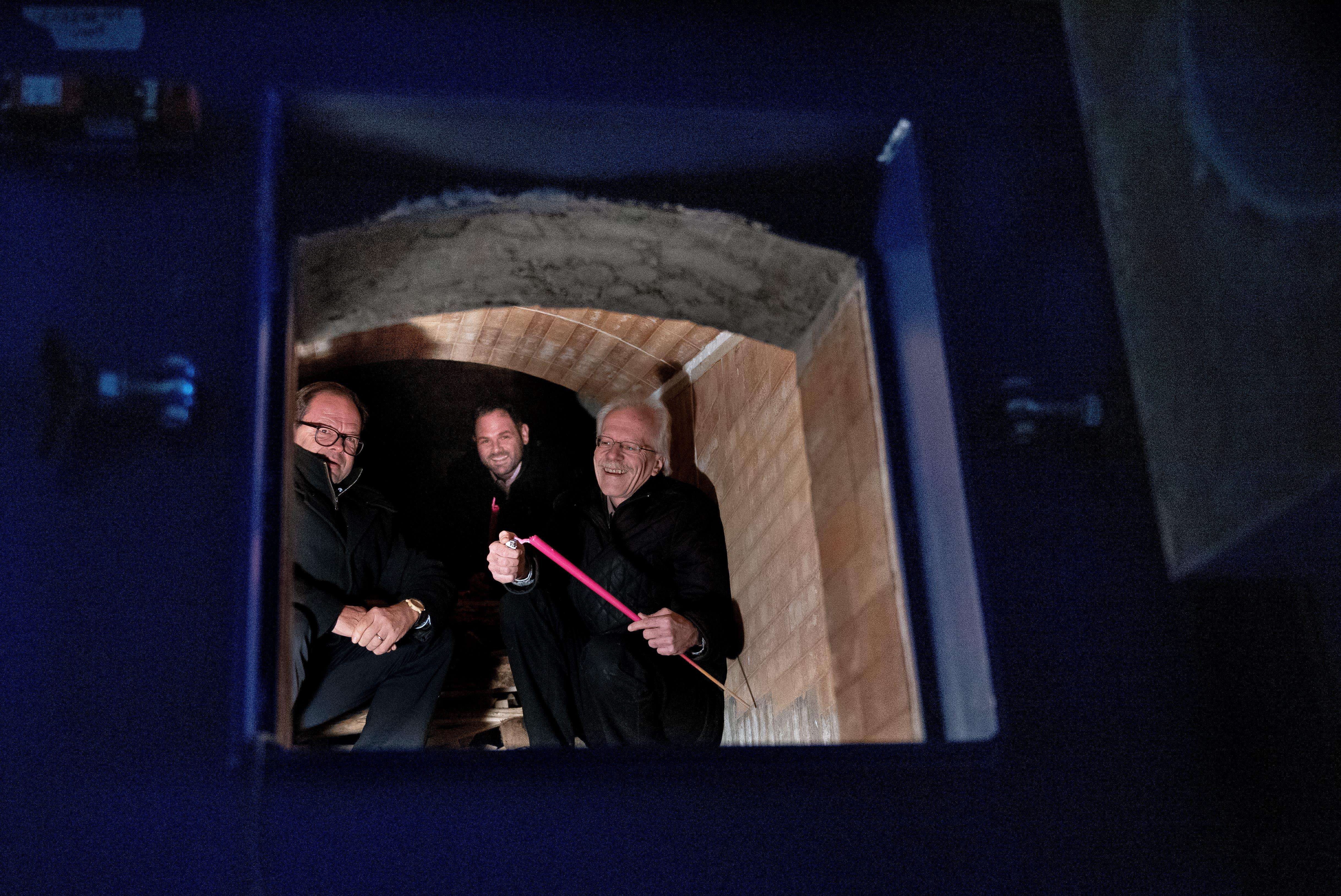 Talammann Alex Höchli  (von rechts) feuert mit Sepp Infanger, Verwaltungsratspräsident der Heizwerk Engelberg AG  und Baudirektor Josef Hess den Ofen ein.