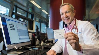 Clarence Davis, ärztlicher Leiter der Permanence im Bahnhof Luzern, zeigt das Ticketsystem. (Bild: Eveline Beerkircher)