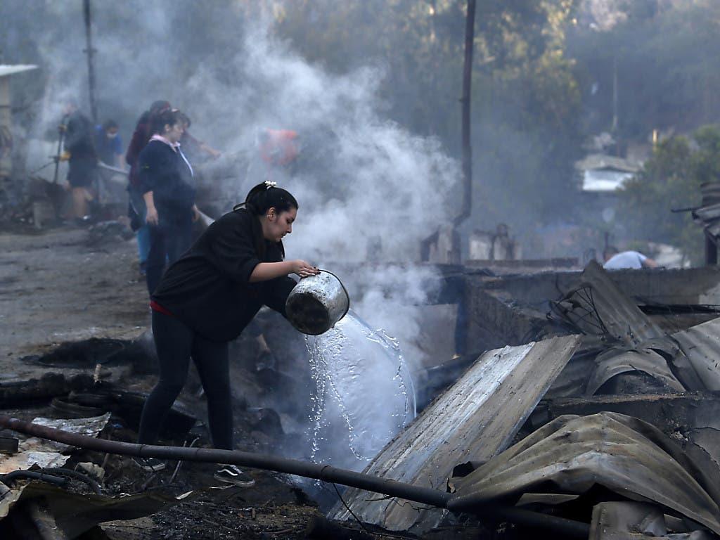 Einwohnerinnen der chilenischen Stadt Valparaíso giessen Wasser auf die Trümmer ihrer Häuser, die von den Bränden zerstört oder beschädigt wurden.