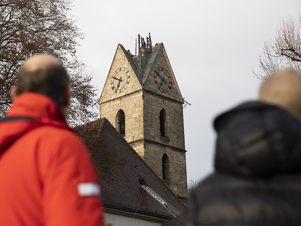 Passanten vor der abgebrannte Spitze des Kirchturms in Herzogenbuchsee.