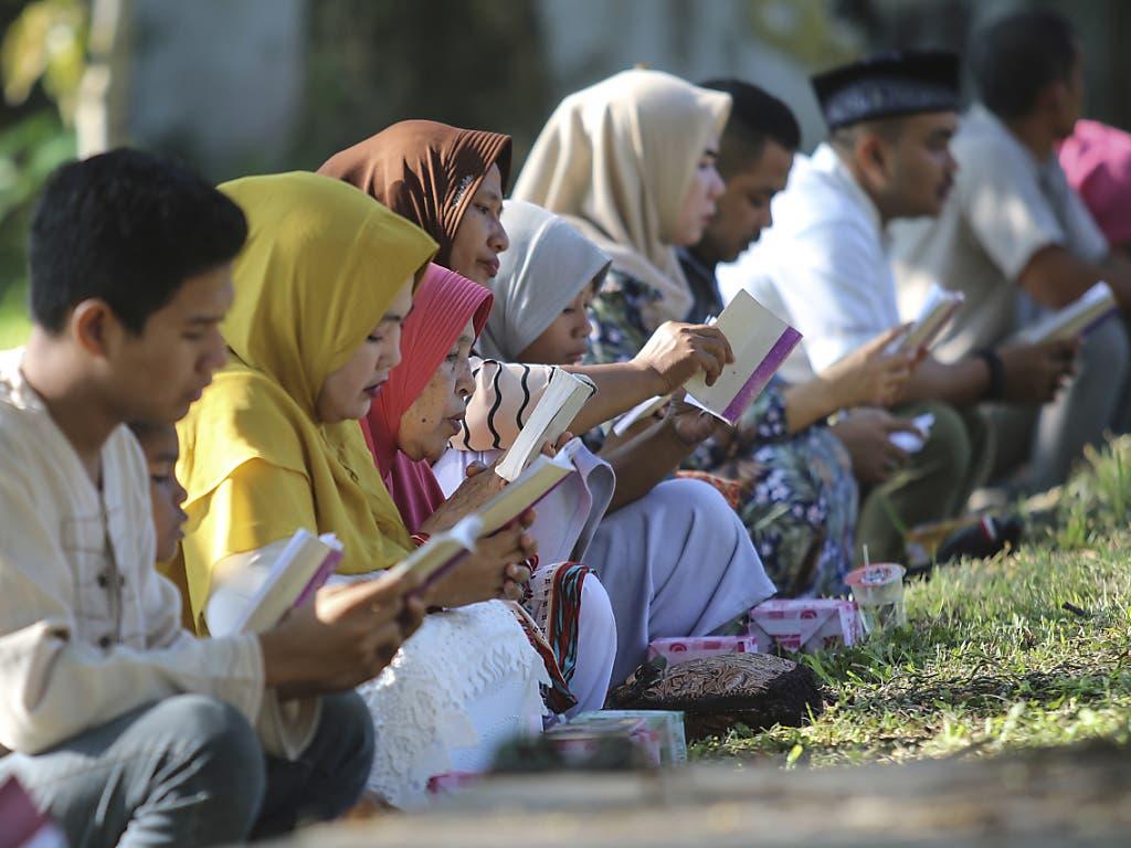 Menschen gedenken bei einem Massengrab in Banda Aceh, Indonesien, der Opfer des verheerenden Tsunamis vom 26. Dezember 2004.