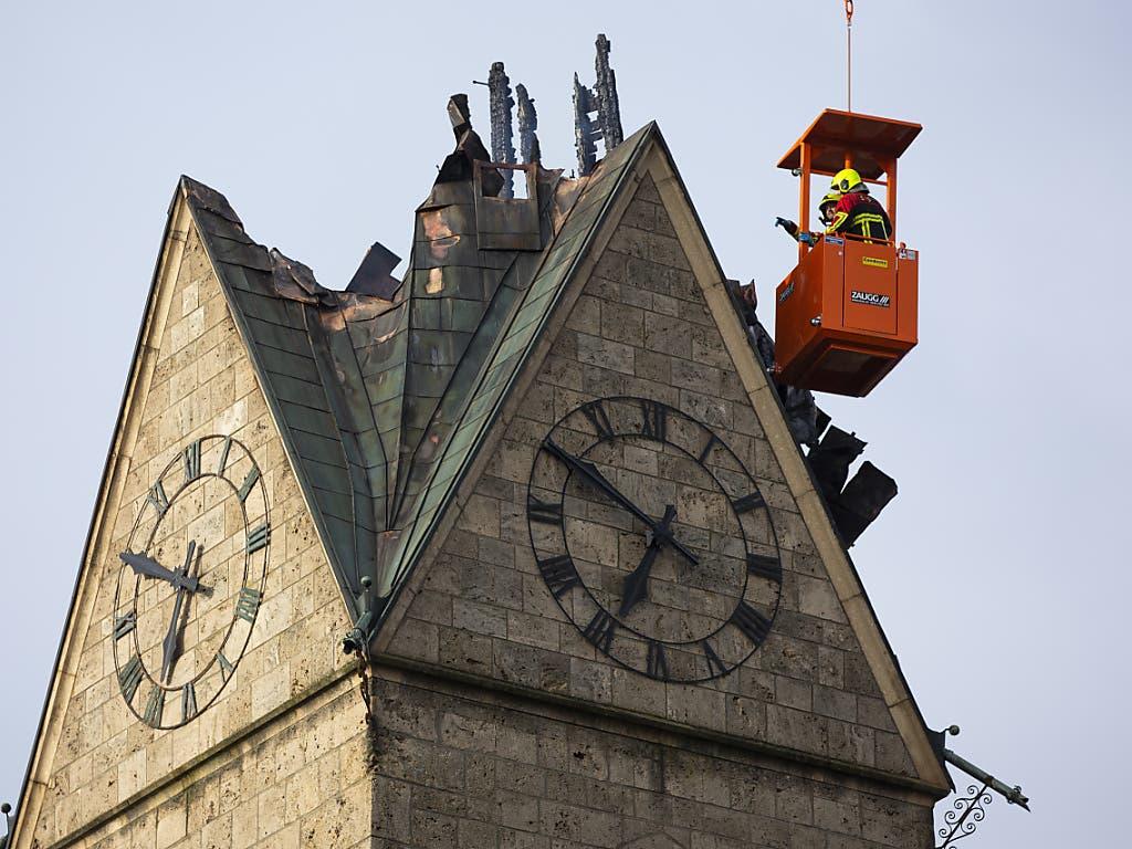 Feuerwehrleute schauen sich die abgebrannte Spitze des Kirchturms der reformierten Kirche von Herzogenbuchsee aus einem Kran an. Das Feuer im Turm der reformierten Kirche hatte an Heiligabend grossen Schaden angerichtet. Ein Teil der Holzkonstruktion stürzte ein und riss ein Loch ins Kirchenschiff.