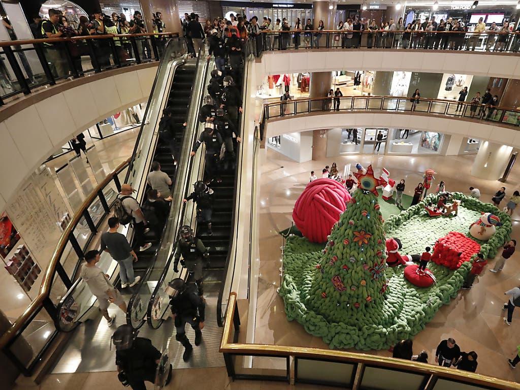 Bereitschaftspolizei und Kunden auf den Rolltreppen des Hongkonger Einkaufszentrums Tsim Sha Tsui.