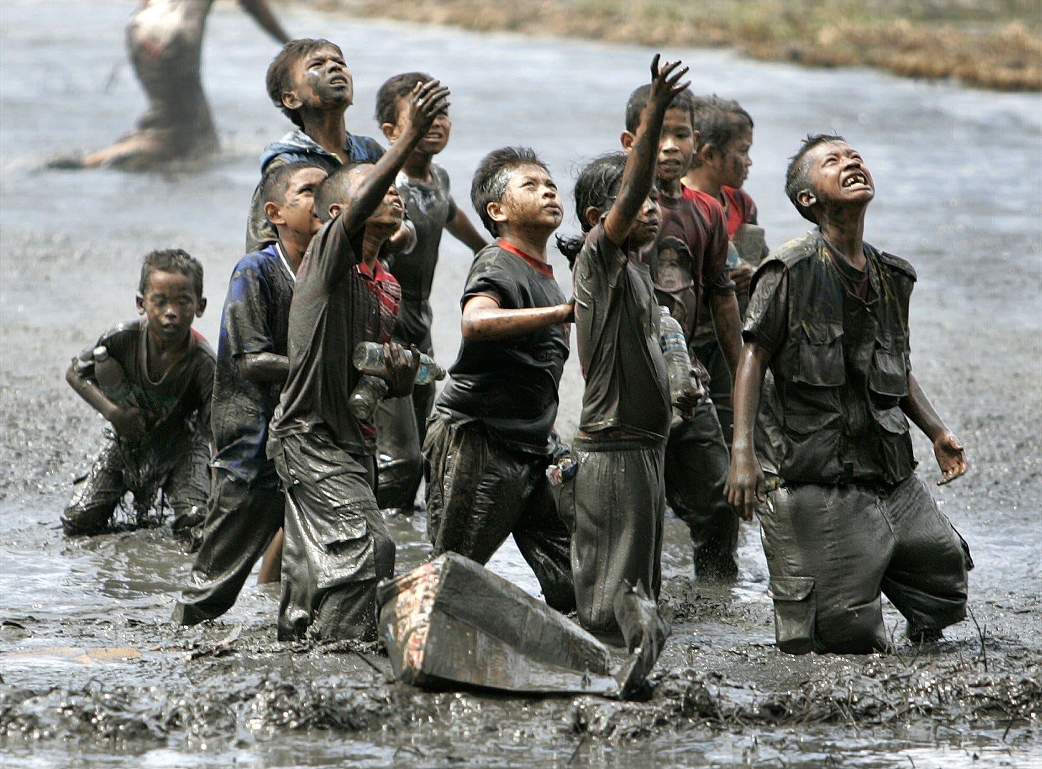 Kinder nehmen rettende Hilfsmittel von Einsatzkräften entgegen.
