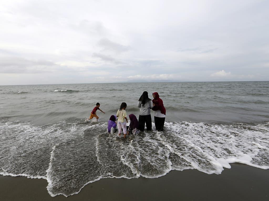 Eine Gruppe von Menschen versammelt sich an einem Strand von Banda Aceh.